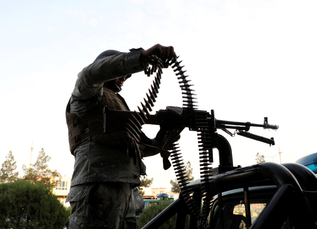 A member of Afghan security forces loads a machine gun near the sit…