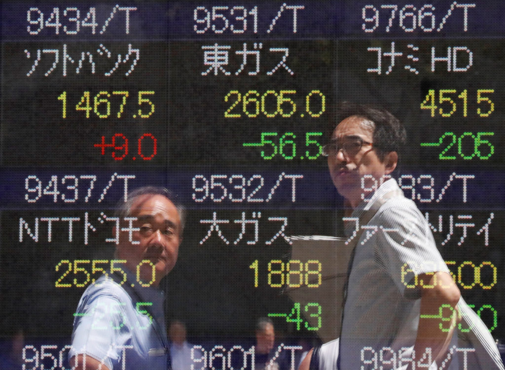 Passersby are reflected on a stock quotation board outside a brokerage in Tokyo, Japan, August 6, 2019. Photo by REUTERS/Issei Kato