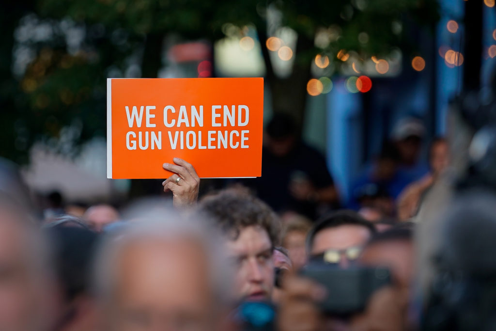 A vigil attendee holds a sign during a vigil at the scene of a mass shooting in Dayton, Ohio, U.S. August 4, 2019. Photo by REUTERS/Bryan Woolston