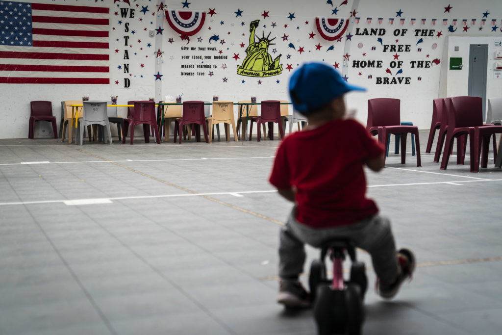 An immigrant child plays in front of patriotic phrases and symbols …