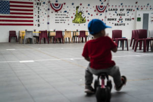 An immigrant child plays in front of patriotic phrases and symbols covering the walls in a gymnasium as U.S. Immigration and Customs Enforcement (ICE) and Enforcement and Removal Operations (ERO) hosts a media tour at the South Texas Family Residential Center, which houses families who are pending disposition of their immigration cases on Friday, Aug. 23, 2019 in Dilley, TX. (Photo by Jabin Botsford/The Washington Post via Getty Images)