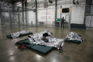 A girl from Central America rests on thermal blankets at a detention facility run by the U.S. Border Patrol on September 8, 2014 in McAllen, Texas. The Border Patrol opened the holding center to temporarily house the children after tens of thousands of families and unaccompanied minors from Central America crossed the border illegally into the United States during the spring and summer. Although the flow of underage immigrants has since slowed greatly, thousands of them are now housed in centers around the United States as immigration courts process their cases. (Photo by John Moore/Getty Images)