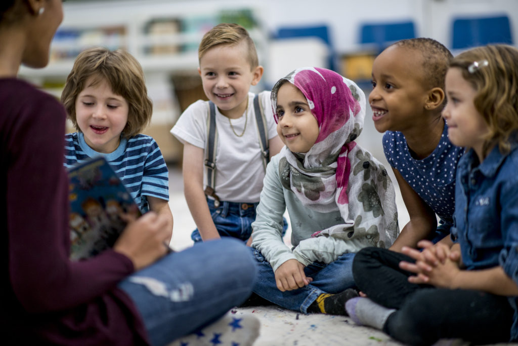 A multi-ethnic group of school children are indoors in a classroom. They are wearing casual clothing. They are sitting on the floor and eagerly listening to their teacher read a storybook.