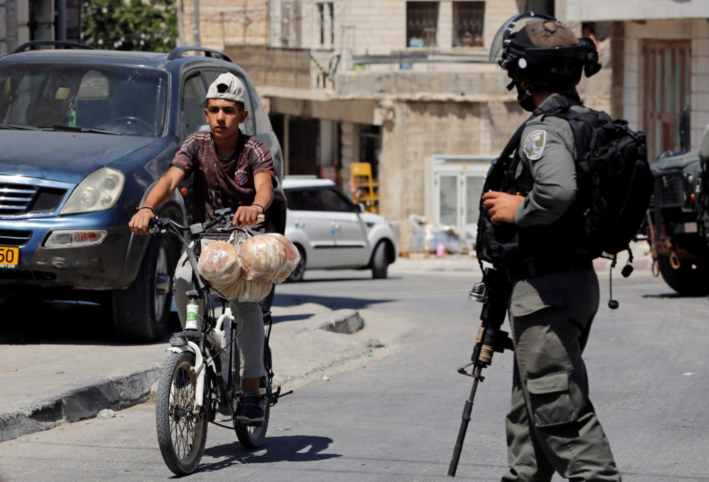 A Palestinian boy rides a bicycle past an Israeli border policeman …