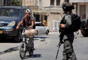A Palestinian boy rides a bicycle past an Israeli border policeman during a raid after the Israeli military said an Israeli soldier was found stabbed to death near a Jewish settlement, in Beit Fajjar in the Israeli-occupied West Bank August 8, 2019. Photo by REUTERS/Mussa Qawasma