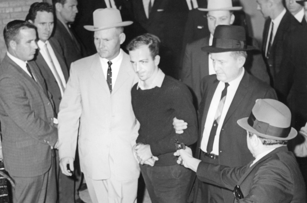 Jim Leavelle (in light suit on the left) escorts Lee Harvey Oswald, who is about to be shot by Jack Ruby. Photo by Jack Beers Jr./Dallas Morning News via Wikimedia Commons