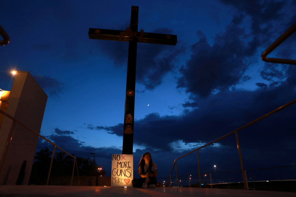 A mourner takes part in a vigil near the border fence between Mexico and the U.S after a mass shooting at a Walmart store in El Paso U.S. in Ciudad Juarez. August 3, 2019. Photo by Carlos Sanchez/Reuters