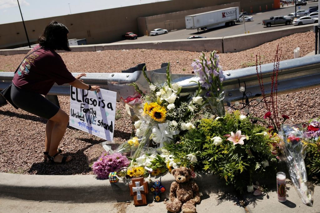 A woman places a placard at the site of a mass shooting where 21 pe…