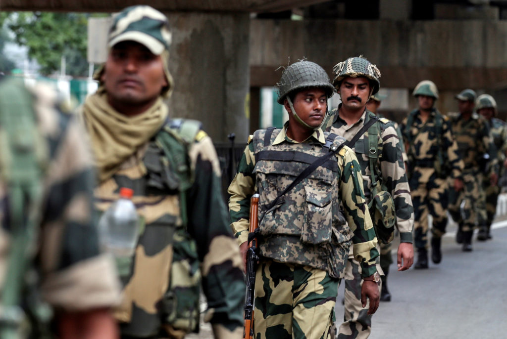 Indian security forces personnel patrol a deserted street during re…