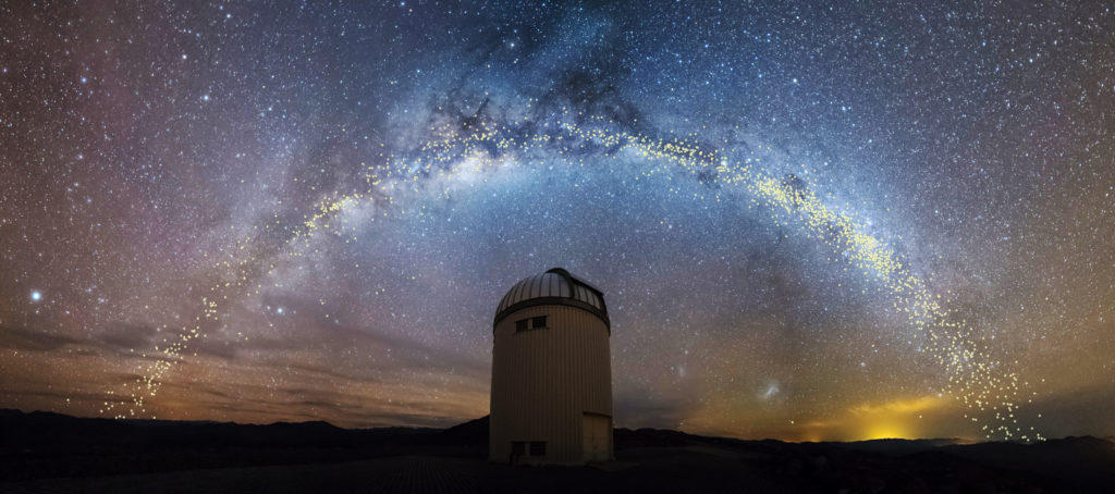 The Milky Way over the Warsaw Telescope. Cepheid stars found by OGLE and used to determine the galaxy's warped shape are shown as yellow dots in the sky. Image by K. Ulaczyk / J. Skowron / OGLE