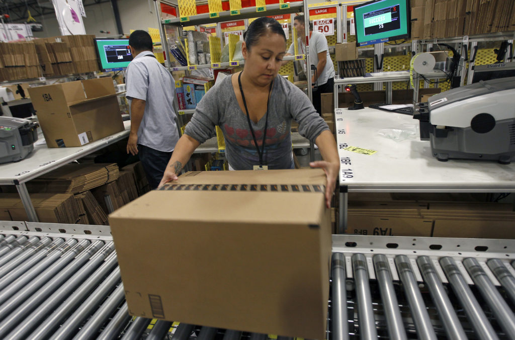 A worker sends a packed item to the shipping department for delivery at Amazon's distribution center in Phoenix, Arizona o...