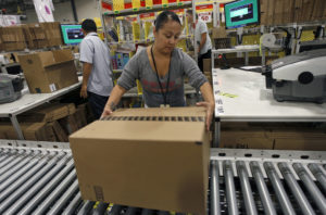 A worker sends a packed item to the shipping department for delivery at Amazon's distribution center in Phoenix, Arizona on November 22, 2013. Photo by Ralph D. Freso/Reuters