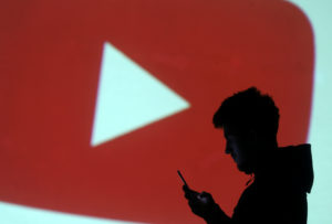 A silhouette of a mobile user is seen next to a screen projection of Youtube logo in this picture illustration taken March 28, 2018. Photo by Dado Ruvic/Illustration via Reuters