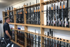 A man looks at firearms on display at Gun City gunshop in Christchurch, New Zealand, March 19, 2019. Since New Zealand began a buyback program, owners have turned in more than 15,000 newly banned guns. Photo by Jorge Silva/Reuters