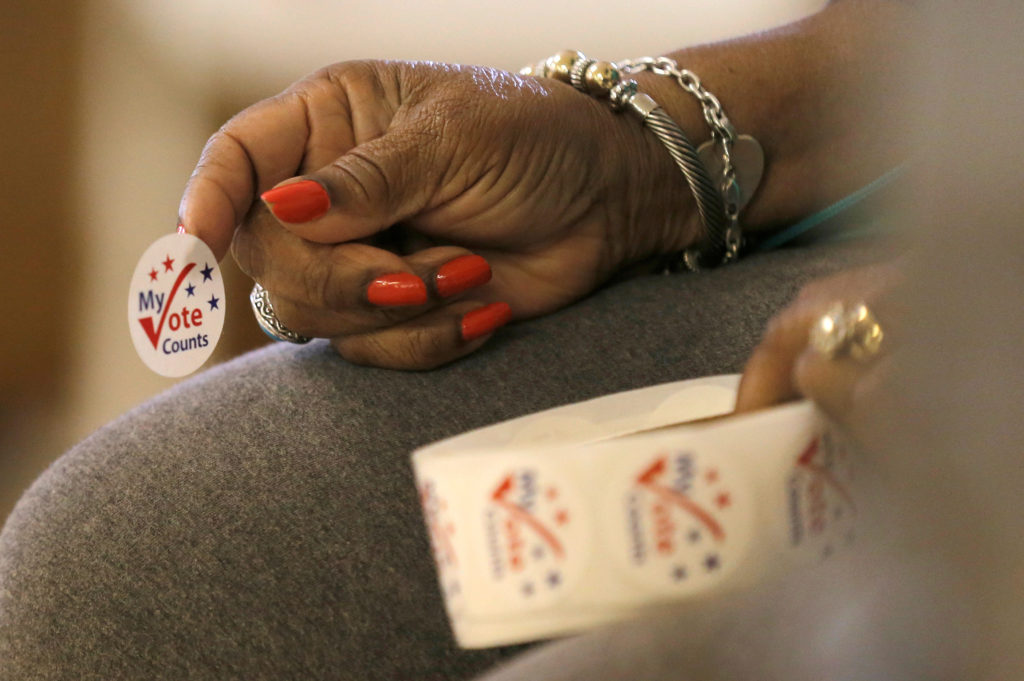 A worker holds stickers for voters at a polling station at the Prin…