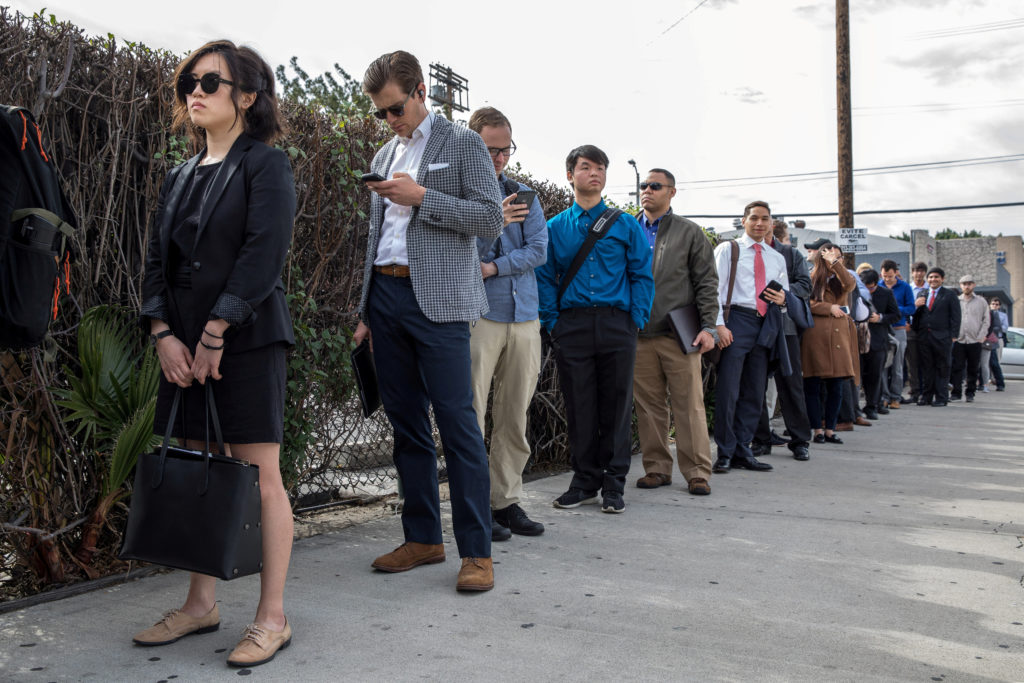 FILE PHOTO: Job seekers line up at TechFair in Los Angeles, California, U.S. March 8, 2018. Photo by Monica Almeida/Reuters