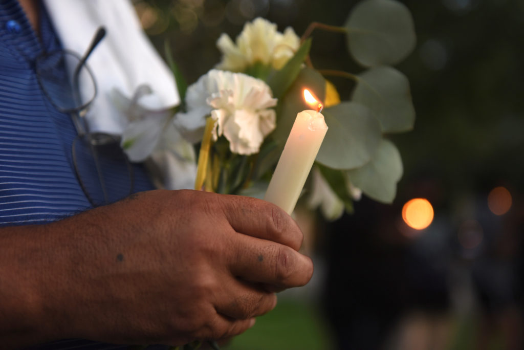 A man holds flowers and a candle as people gather for a vigil follo…