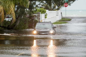 A car drives through a flooded street after the effects of Hurricane Dorian arrived in Nassau, Bahamas, September 2, 2019. Photo by John Marc Nutt /Reuters
