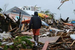 A man walks through the rubble in the aftermath of Hurricane Dorian on the Great Abaco island town of Marsh Harbour, Bahamas, September 2, 2019. Picture taken September 2, 2019. Photo by Dante Carrer/Reuters