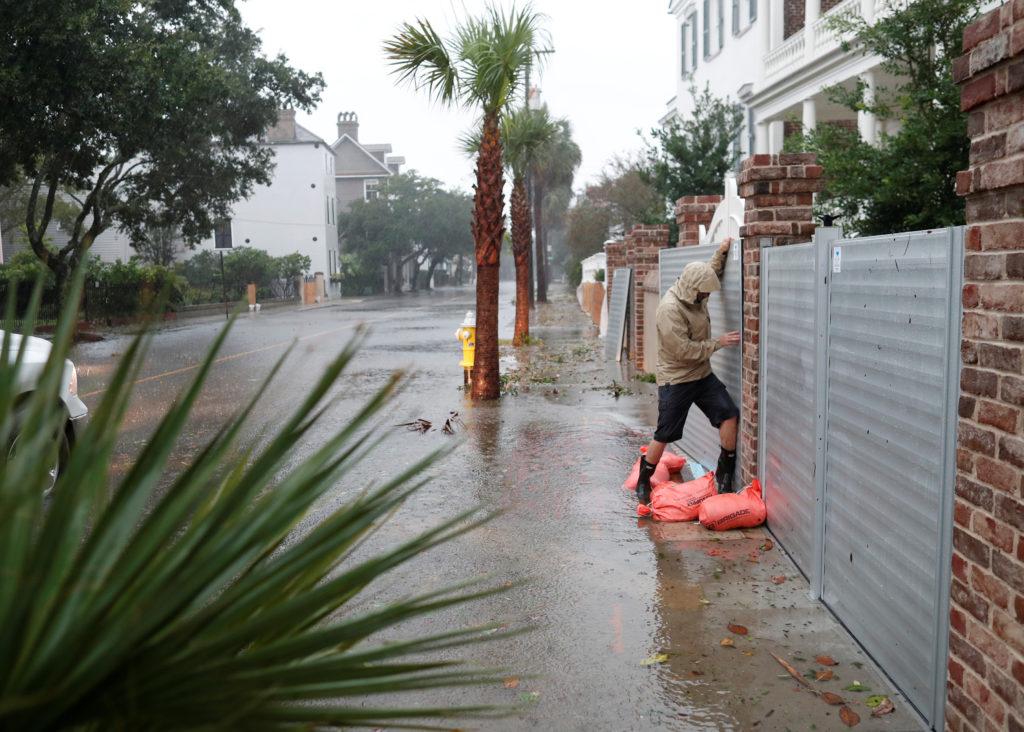 Brys Stephens struggles to install a metal flood gate along South B…