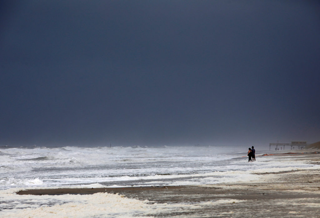 A couple look out at the roiling surf while the skies darken as Hur…