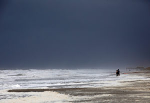 A couple look out at the roiling surf while the skies darken as Hurricane Dorian approaches, in Carolina Beach, North Carolina, on September 5, 2019. Photo by Jonathan Drake/Reuters