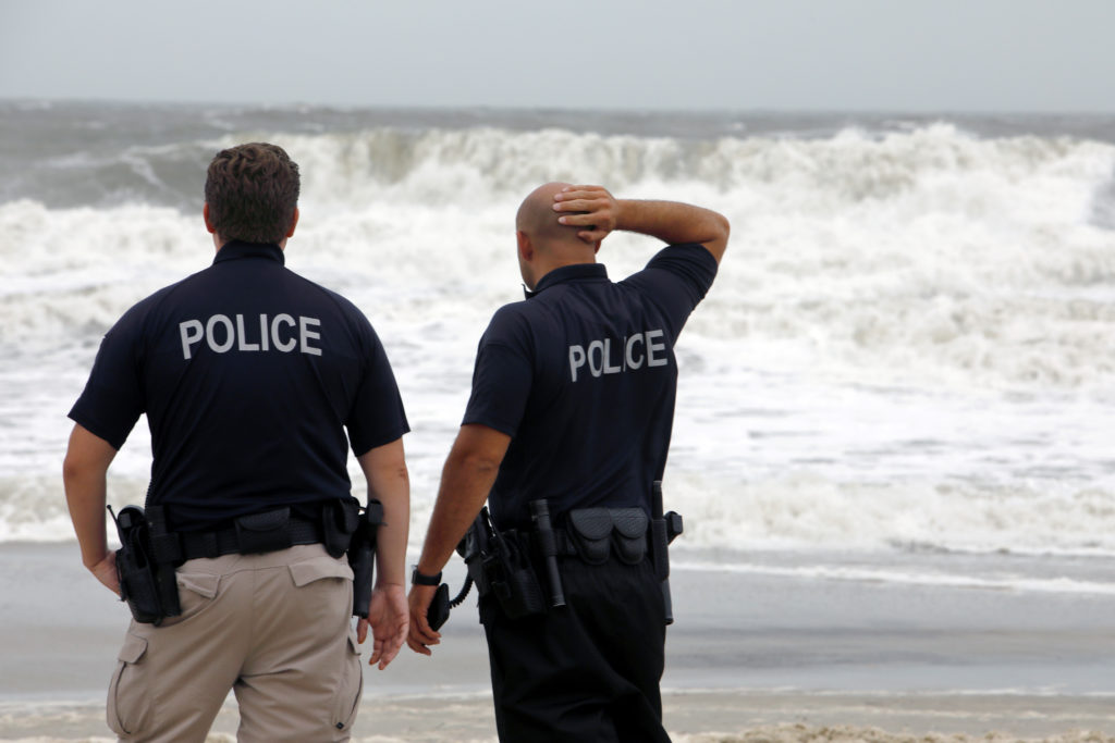 Police officers survey the increasingly rough surf as Hurricane Dorian approaches, in Carolina Beach, North Carolina, on September 5, 2019. Photo by Jonathan Drake/Reuters