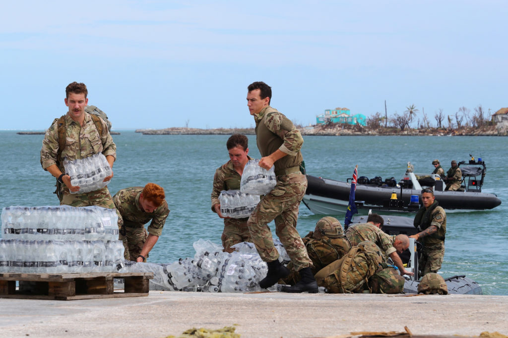 Members of the Humanitarian and Disaster Relief (HADR) team from the Royal Fleet Auxiliary's RFA Mounts Bay deliver suppli...