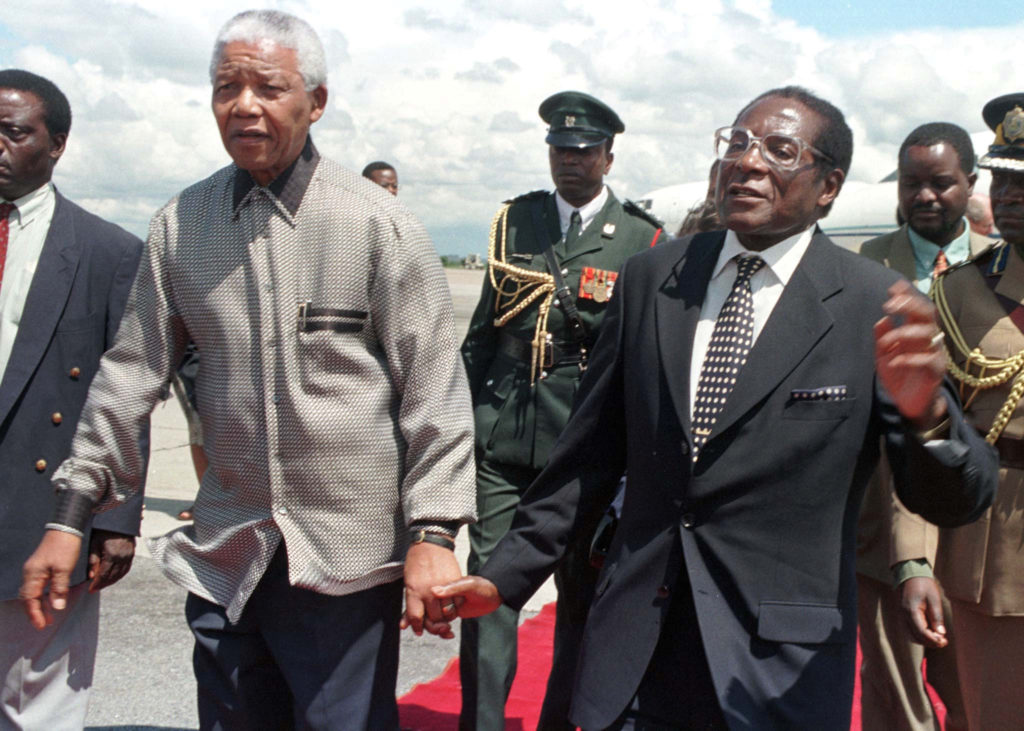 President Robert Mugabe of Zimbabwe (right) holds hands with his South African counterpart Nelson Mandela greeting him on his arrival in the country December 13, 1998. Photo by Howard Burditt/Reuters