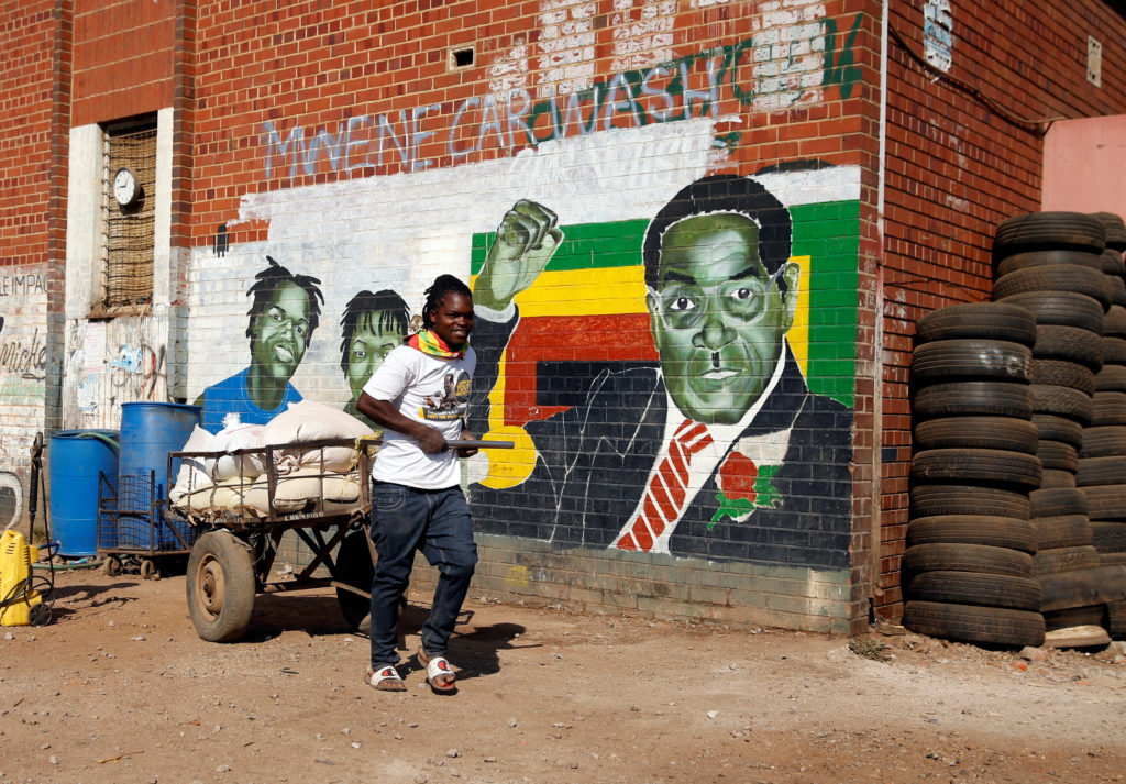 A youth pushes a cart loaded with maize for sale nearby a mural depicting Zimbabwe's former President Robert Mugabe, after hearing the news of his death, in Mbare in the capital Harare, Zimbabwe, September 6, 2019. Photo by Philimon Bulawayo/Reuters