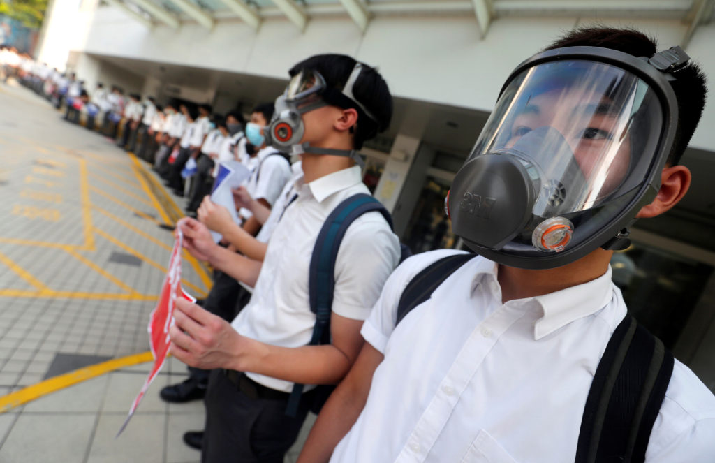 Secondary school students wearing masks join a human chain protesting against what they say is police brutality against pr...