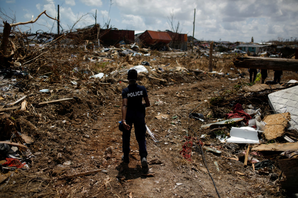 A police officer searches for the dead in the destroyed Mudd neighborhood after Hurricane Dorian hit the Abaco Islands in ...