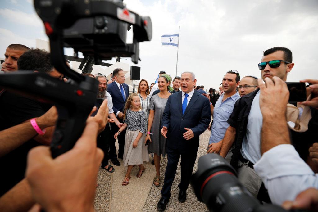 Members of the media work as Israeli Prime Minister Benjamin Netanyahu walks after holding a weekly cabinet meeting in the...