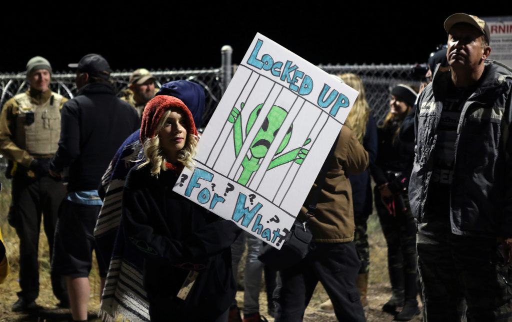 A woman carries a sign outside a gate to Area 51 as an influx of tourists responding to a call to 'storm' Area 51, a secre...