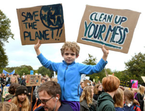 A child holds placards during a protest march to call for action against climate change, in The Hague, Netherlands September 27, 2019. Photo by REUTERS/Piroschka van de Wouw