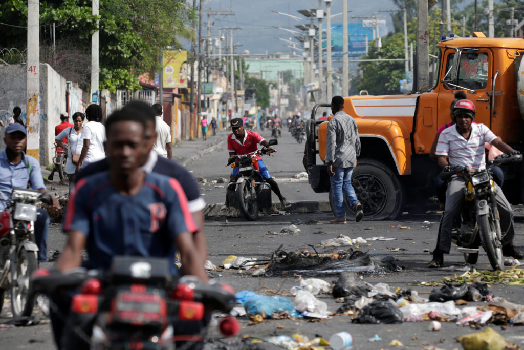 Men riding motorbikes pass on the side of a barricade made of truck and a pole blocking a street in Port-au-Prince, Haiti ...