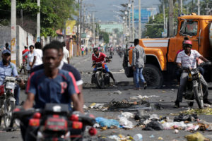 Men riding motorbikes pass on the side of a barricade made of truck and a pole blocking a street in Port-au-Prince, Haiti September 29, 2019. Photo by Andres Martinez Casares/Reuters