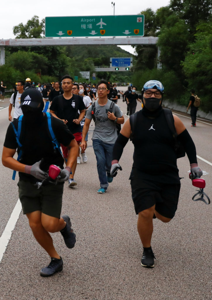 Protesters run away from police on the road leading to Hong Kong International Airport on September 1, 2019. Photo by Kai Pfaffenbach/Reuters