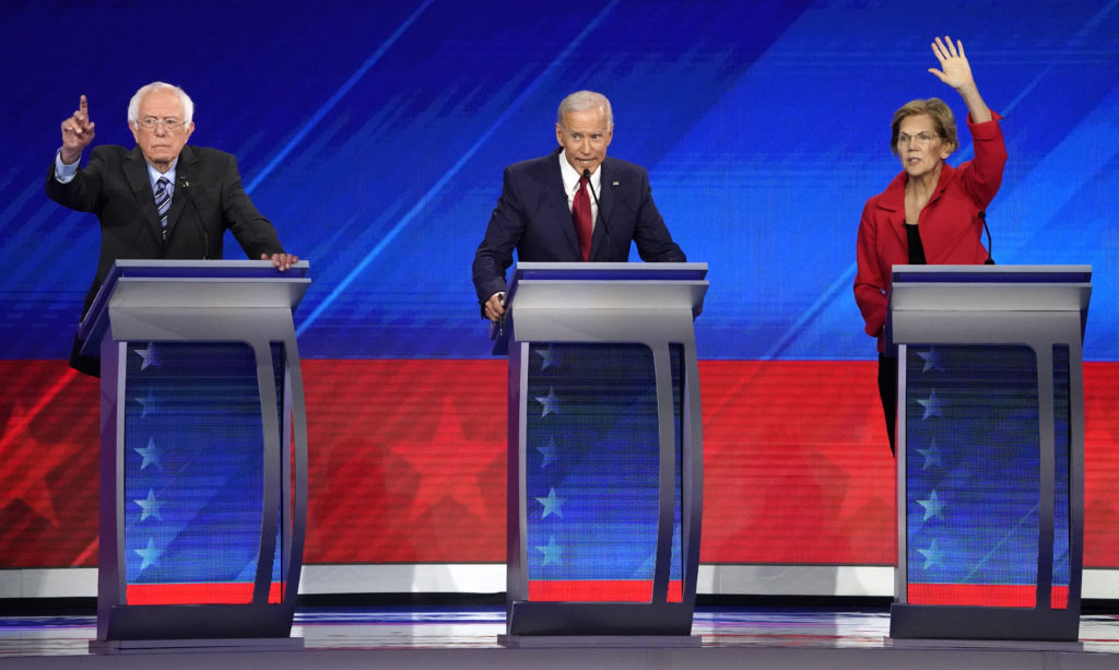 Senator Bernie Sanders, former Vice President Joe Biden and Senator Elizabeth Warren (L-R) try to get the moderators atten...