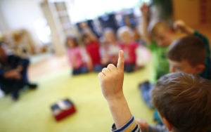 Children gesture as they sit in a playing circle at their kindergarten run by a private foundation which is not affected by the nursery caretakers strike in Hanau, 30km south of Frankfurt, Germany, May 8, 2015. Most of the kindergartens run by public services all over Germany face a strike of the nursery caretakers as they fight for higher wages and better working conditions.