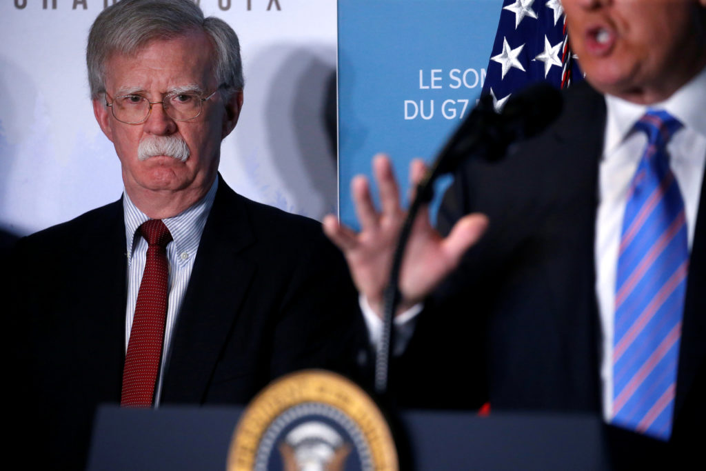 U.S. National Security Advisor John Bolton watches as U.S. President Donald Trump gives a news briefing at the G7 Summit in the Charlevoix city of La Malbaie, Quebec, Canada June 9, 2018. REUTERS/Leah Millis - RC131E473EE0