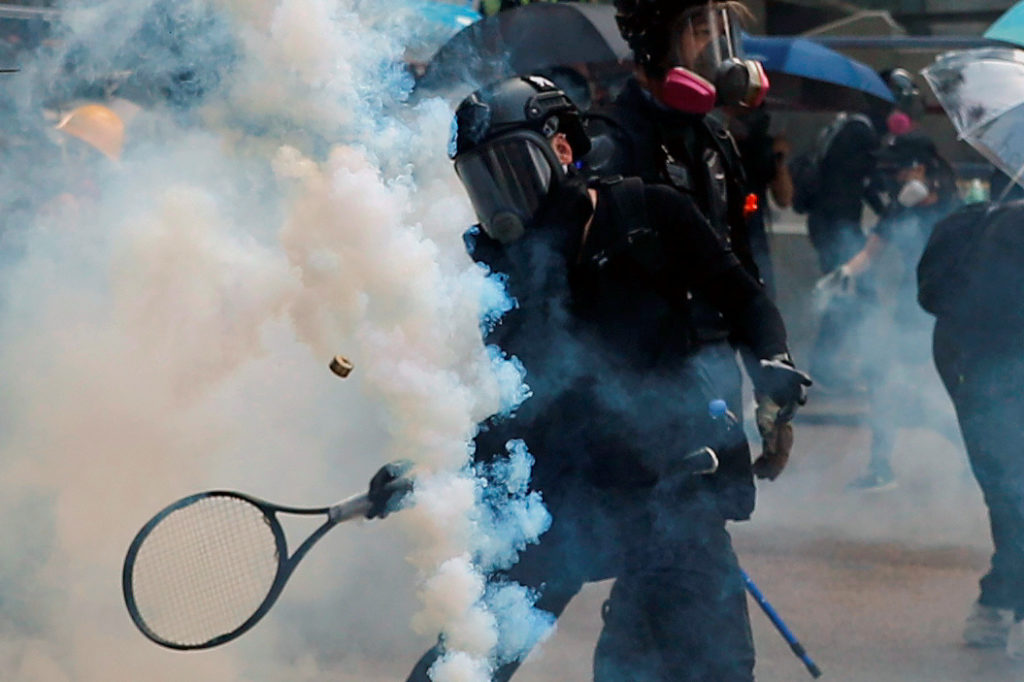 An anti-government protester uses a tennis racket to hit a tear gas canister during a clash with riot police in Hong Kong on September 29, 2019