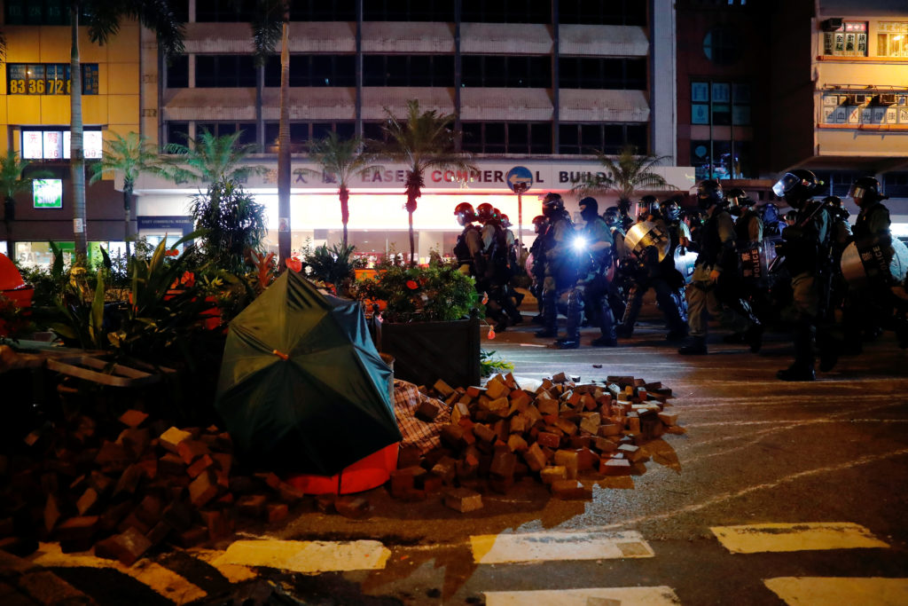 Riot police walk past a barrier after a clash with anti-government …