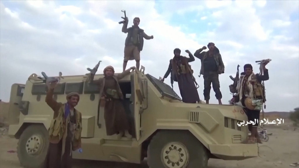 Houthi fighters pose on an alleged captured Saudi vehicle after an attack near the border with Saudi Arabia's southern region of Najran in Yemen, in this still image taken from video on September 29, 2019.