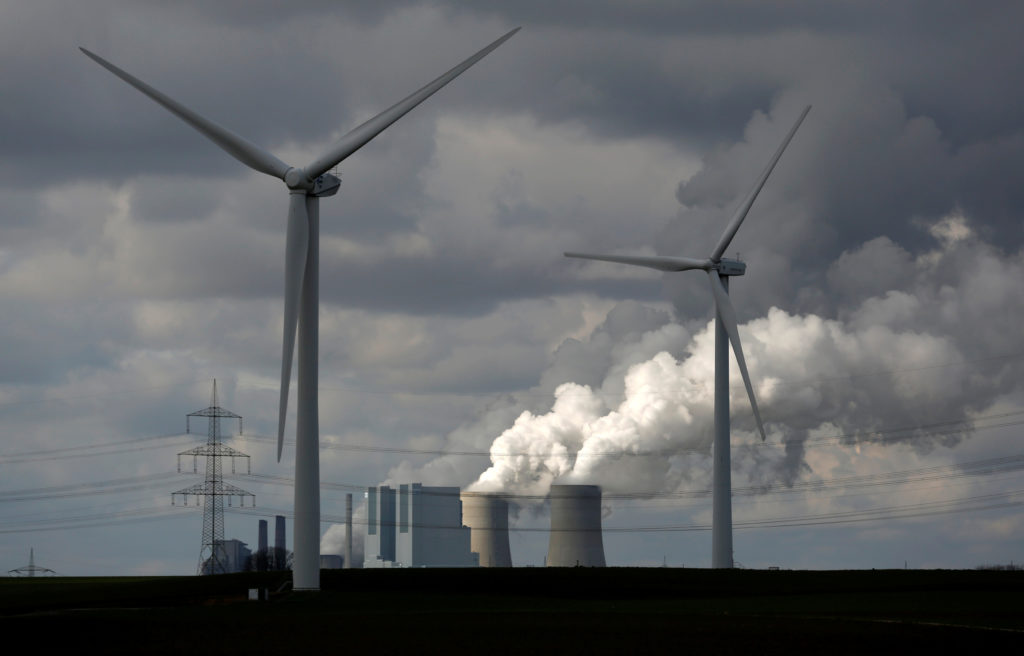 Wind turbines are seen in front of a coal power plant of German utility RWE Power near the western town of Neurath February 28, 2014. Photo by REUTERS/Ina Fassbender