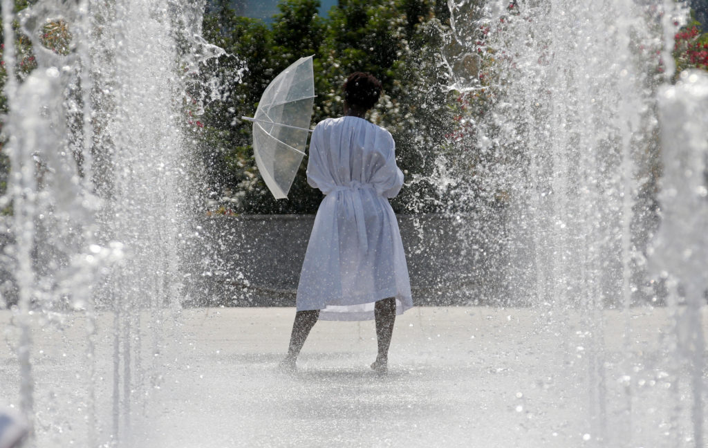 A woman cools off in water fountains in a park as hot summer temperatures hit Paris, France, June 22, 2017. Photo by REUTERS/Jean-Paul Pelissier