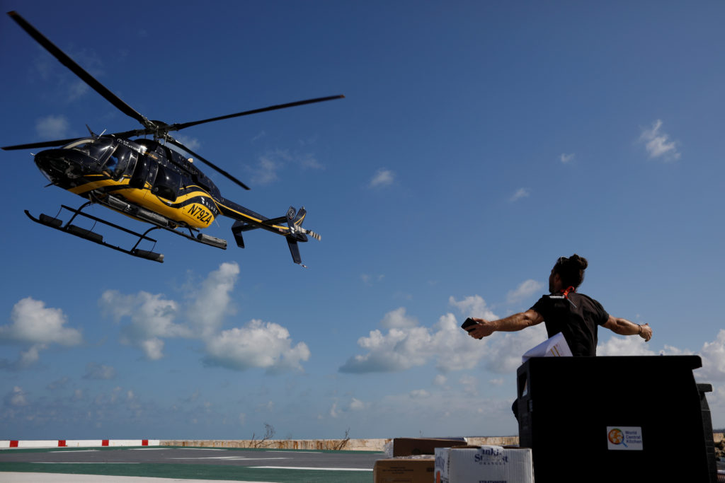 A volunteer of the NGO World Central Kitchen gestures as a helicopter leaves after delivering food for distribution, after Hurricane Dorian hit the Abaco Islands in Marsh Harbour, Bahamas, September 10, 2019. Picture taken September 10, 2019. Photo by REUTERS/Marco Bello