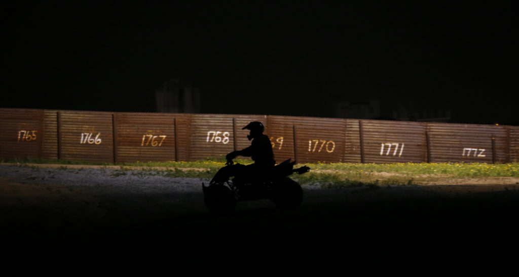 A U.S. Border Patrol agent patrols on his ATV along the primary fence on the international border between Mexico and the United States near San Diego, California March 26, 2013. Some of the border fencing includes Vietnam-era landing mats. Photo by Mike Blake/Reuters