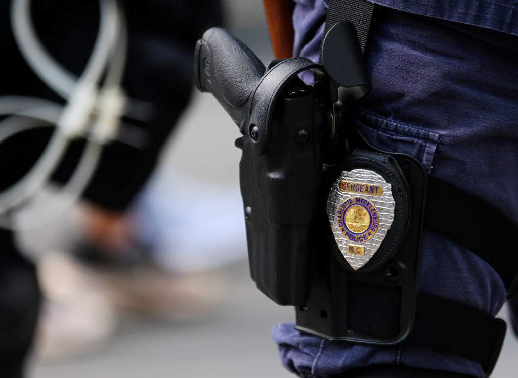FILE PHOTO: The badge and gun of a Charlotte police officer in riot gear are seen during a large security presence outside the football stadium as the NFL's Carolina Panthers host the Minnesota Vikings amid protesting of the police shooting of Keith Scott in Charlotte, North Carolina, U.S., September 25, 2016. Photo by Mike Blake/Reuters