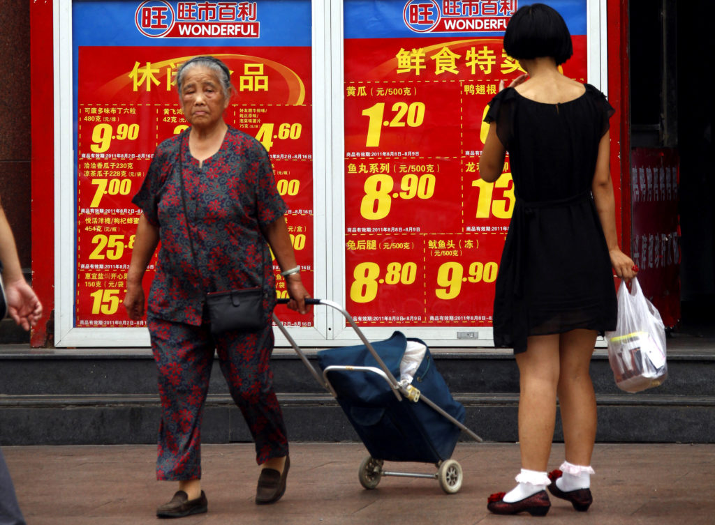 FILE PHOTO: Shoppers walk past and look at a board displaying food prices at a shopping mall in central Beijing August 9, ...